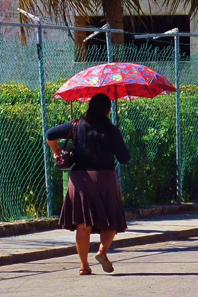 Woman in Playa Del Carmen walking with umbrella