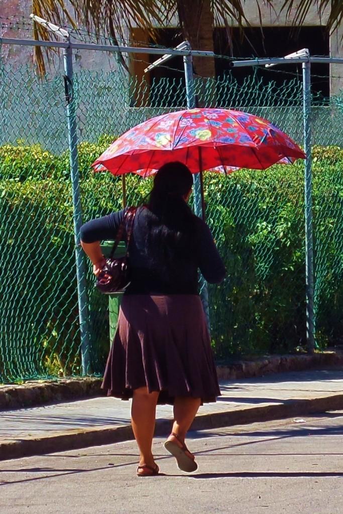 Woman in Playa Del Carmen walking with umbrella